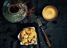 Blueberry Crumb Muffins and coffee. Top view on Blueberry Muffins on a black linen surrounded with fresh blueberries, a fork, vintage vase and a cup of coffee in Stock Images