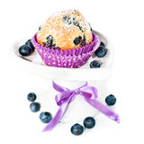 Blueberry cupcake on a decorated plate isolated on white. Blueberry muffin and some berries on a white plate, isolated stock photo