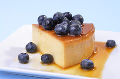 Blueberry flan. Horizontal shot of delicious slice of flan cheesecake topped with fresh blueberries on blue background Stock Photo