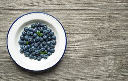Fresh Blueberry with leaves in plate royalty free stock photos