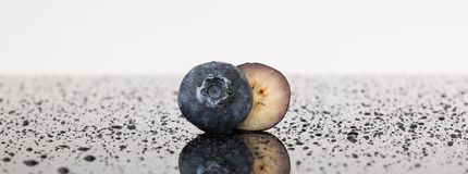 Blueberry in half isolated on white background on a reflective surface surrounded by water droplets. Sweet Beautiful Blueberry in half isolated on white royalty free stock photos