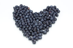 Blueberry Heart. Blue purple fruit berry in the shape of love on a reflective white background Royalty Free Stock Photos