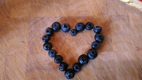 Blueberry heart. Purple blueberry heart Stock Images