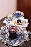 Blueberry home made jam. Home made blueberry jam in a glass jar on a silver tray prepared for breakfast at home Stock Image