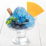 Blueberry ice cream cup. Blue ice cream in cup with blueberry fruits on white rustic wooden background stock photo