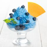 Blueberry ice cream in cup. Blue ice cream in cup with blueberry fruits on white wooden background royalty free stock image