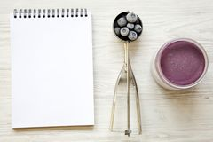 Blueberry ice cream sorbet in plastic jar, icecream scoop with frozen blueberries and notepad on a white wooden background, from a. Bove. Top view stock image