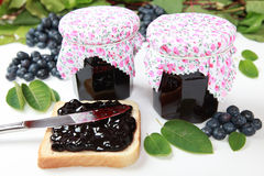 Blueberry jam. Two glasses of homemade blueberry jam with fresh fruits, toast and leaves royalty free stock images