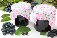 Blueberry jam. Two glasses of homemade blueberry jam with fresh fruits and leaves royalty free stock image