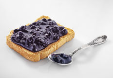 Blueberry jam. Slice of bread covered with blueberry jam Stock Photos