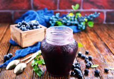 Blueberry jam. In glass bank and on a table stock photo