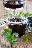 Blueberry jam in glass jar on wooden table Stock Photos