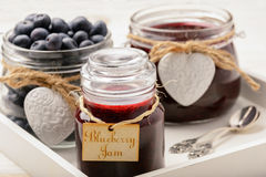 Blueberry jam in glass jars on white wooden background. Selective focus. Royalty Free Stock Photos