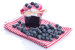 Blueberry jam jar with fresh blueberries. On dish towel, isolated on white Royalty Free Stock Photo