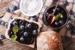 Blueberry jam and sweet bun close-up on the table. horizontal to Stock Photography