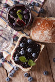 Blueberry jam and sweet bun close-up on the table. Vertical top Stock Photo
