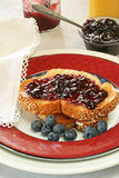 Blueberry jam toast. Breakfast setting with toast, blueberry jam, fresh blueberries and orange juice; white cloth napkin on side Stock Images