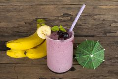 Blueberry Juice and Banana smoothies, a tasty healthy drink in a glass, drink the morning on a wooden background. Blueberry mix banana smoothie purple colorful royalty free stock photography