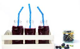 Blueberry juice bottles in a white wooden box. Isolated Stock Photos