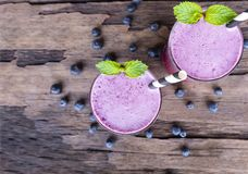 Blueberry Juice smoothies a tasty healthy drink in a glass drink the morning on a wooden background from the top view. Blueberry smoothie purple colorful fruit royalty free stock photo