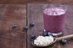 Blueberry Kefir Smoothie and Kefir Grains. Kefir grains in wooden spoon in front of Blueberry Kefir Smoothie. Kefir is one of the top health foods available Royalty Free Stock Photography