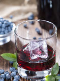 Blueberry Liqueur. Homemade Blueberry Liqueur with fresh fruits on wooden background stock photo