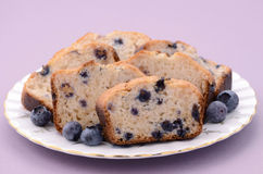 Blueberry loaf slices. With afternoon tea on mauve background Royalty Free Stock Photo