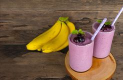 Blueberry Juice and Banana smoothies, a tasty healthy drink in a glass, drink the morning on a wooden background. Blueberry mix banana smoothie purple colorful royalty free stock photos