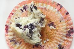 Blueberry Muffin. A half eaten blueberry muffin sits on a colorful wrapper Royalty Free Stock Photography