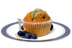 Blueberry muffin. On a china plate with silver fork isolated on white Stock Photos