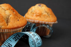 Blueberry Muffin Diet 3. This is an image of blueberry muffins and a measuring tape. This is a metaphor for dieting stock photography