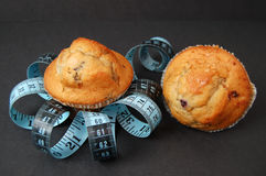 Blueberry Muffin Diet 4. This is an image of blueberry muffins and a measuring tape. This is a metaphor for dieting royalty free stock photography