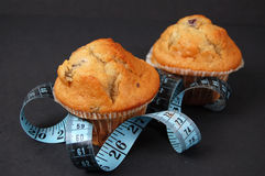 Blueberry Muffin Diet. This is an image of blueberry muffins and a measuring tape. This is a metaphor for dieting royalty free stock photo