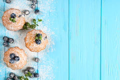 Blueberry muffin. Homemade baked cupcake with blueberries, fresh berries, mint, powdered sugar on blue wooden background. Top view Royalty Free Stock Photography