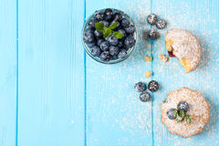 Blueberry muffin. Homemade baked cupcake with blueberries, fresh berries, mint, powdered sugar on blue wooden background. Top view Stock Photo
