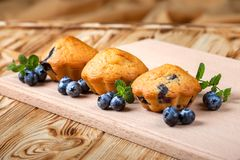 Blueberry muffin. Homemade baked cupcake with blueberries, fresh berries, mint on wooden background. Empty space for text. Stock Photos