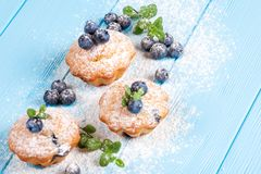Blueberry muffin. Homemade baked cupcake with blueberries, fresh berries, powdered sugar on blue wooden background. Top view. Stock Images