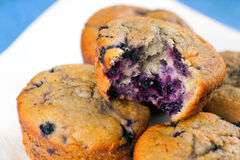 Blueberry Muffins. On a wooden plate showing the berries inside Stock Image
