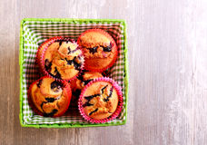 Blueberry muffins in basket over wooden surface Royalty Free Stock Images