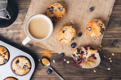 Blueberry muffins breakfast on a rustic table. Freshly baked blueberry muffins with almond, oats and icing sugar topping on a rustic wooden table and a mug of stock image