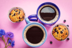 Blueberry muffins, two cups of coffee and cornflowers on pink ba. Ckground Royalty Free Stock Images