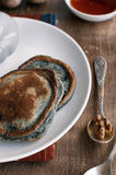 Blueberry pancake. Blue pancakes lie on a white round plate, on the wooden table Stock Image