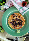 Blueberry pancake on green plate served with maple syrup Royalty Free Stock Images