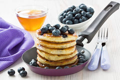 Blueberry pancakes. With honey, maple syrup and berries in frying pan Stock Photo