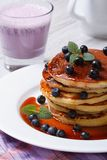 Blueberry pancakes with maple syrup and a cocktail close-up Stock Images