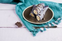 Blueberry pancakes stuffed with whole banana wrapped in a tube and poured with chocolate Royalty Free Stock Photography
