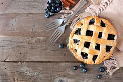 Blueberry pie, top view corner border over a rustic wood background. Rustic homemade blueberry pie with lattice pastry. Top view scene. Corner border with copy stock image