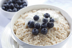 Blueberry Porridge. Bowl of oatmeal porridge, topped with fresh blueberries and yogurt. Healthy, delicious variation of a traditional Scottish breakfast stock image