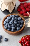 Blueberry, raspberries, redcurrant in bowl and jam in jar. Mixed berries Stock Photography