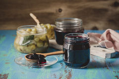 Blueberry,  raspberry and gooseberry jam in glass jars on blue r Stock Photo